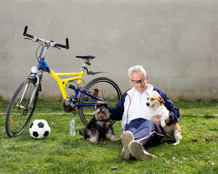 Senior man sitting on grass with dogs after bike ride photo