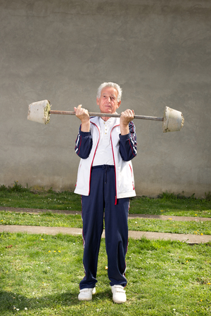loose skin: Senior man lifting homemade weights from concrete blocks