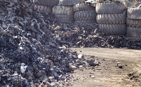 dump yard: Close up of shredded tire pile and old used tires in background