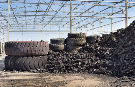 dump yard: Close up of old used tires and shredded tire pile in background Stock Photo