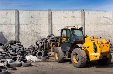dump yard: Dredger grabbing automobile tires into bucket for recycling