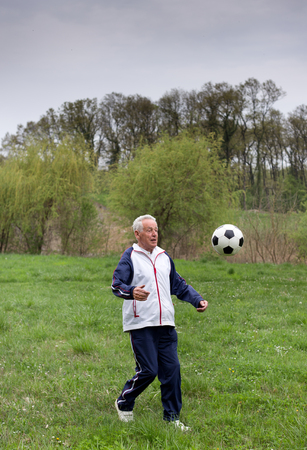 Old man in seventies kicking a soccer ball in park photo