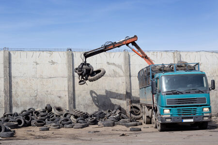 dump yard: Unloading old used tires from truck for recycling