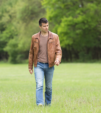 Attractive young man walking alone in forest