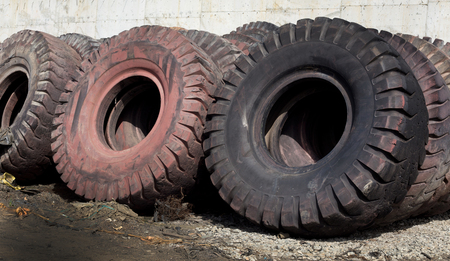 dump yard: Old used tires for recycling standing against the wall Stock Photo
