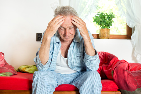 Old man sitting on bed and holding head with hands photo