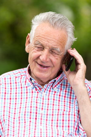 Old man smiling and talking on cell phone photo