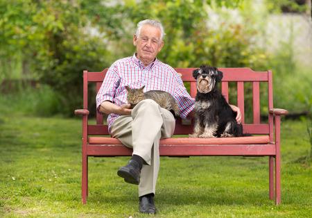 persona mayor: El viejo hombre descansando en el banco y que abraza el perro y el gato
