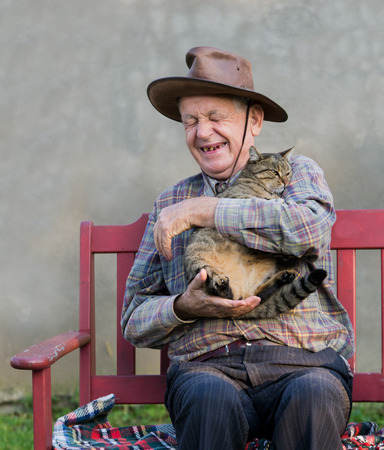 purring: Old man hugging his cat and laughing Stock Photo