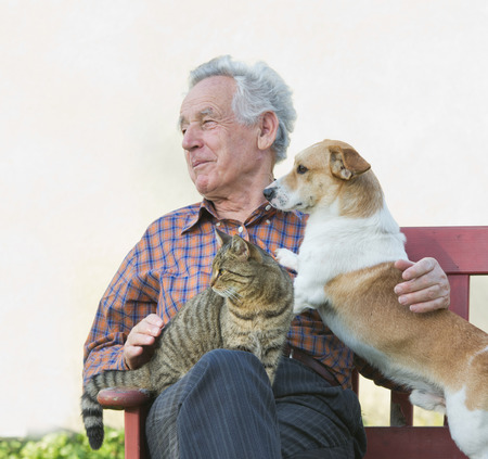 Senior man with dog and cat on his lap in garden photo