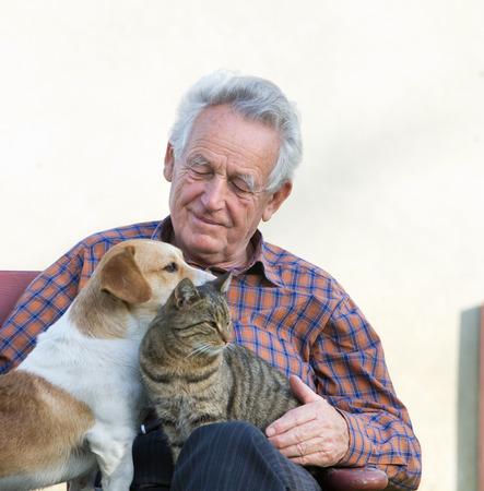 grandfather: Hombre mayor con el perro y el gato en su regazo en el jardín Foto de archivo