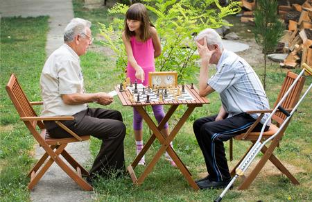 jugando ajedrez: La chica joven muestra su abuelo cómo jugar al ajedrez Foto de archivo