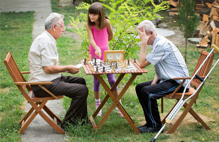 playing chess: Young girl shows her grandpa how to play chess