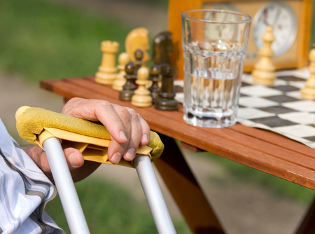 Pensioner with crutches playing chess photo