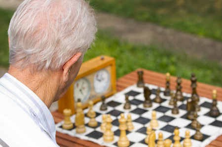Pensioner playing chess in courtyard photo