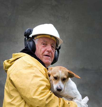 Old man in safety suit holds dog in his arms photo