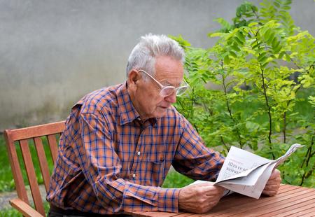 old furniture: Pensioner reading newspaper in garden