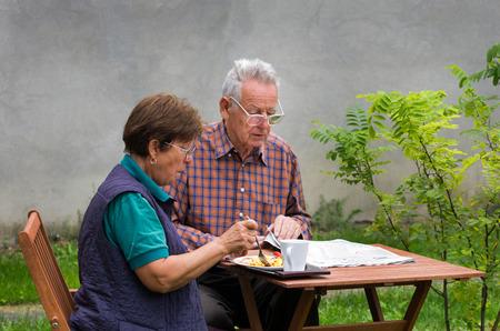 Senior couple sitting in garden in morning photo