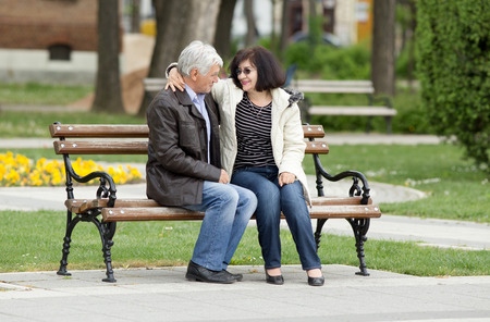 Older couple in hug sitting on bench in park