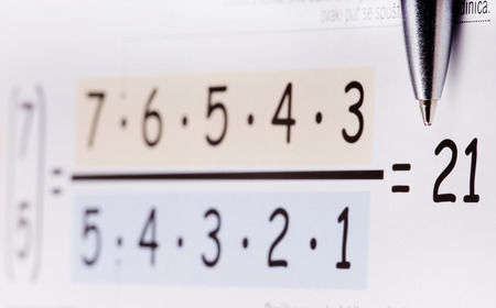 Figures implementing in formula and pencil pointing at result photo