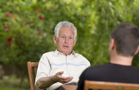 Ernstige oude man praten met kleinzoon en het uitleggen van de hand
