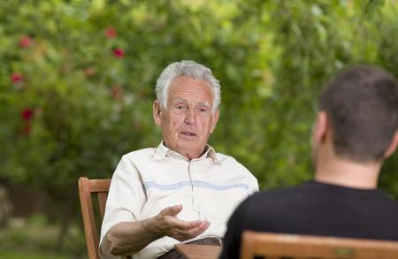 Sérieux vieil homme parlant avec petit-fils et d'expliquer à la main