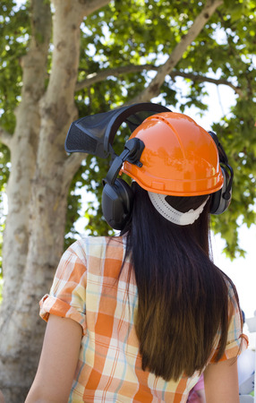 Young girl in plaid shirt wearing orange helmet with earphones from back photo