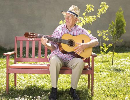 Uomo anziano con il cappello di paglia a suonare la chitarra acustica sulla panchina