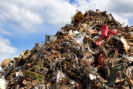 Pile of metal waste for recycling, blue sky and white clouds in background