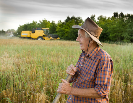 Smiling old peasant standing on field with combine in background