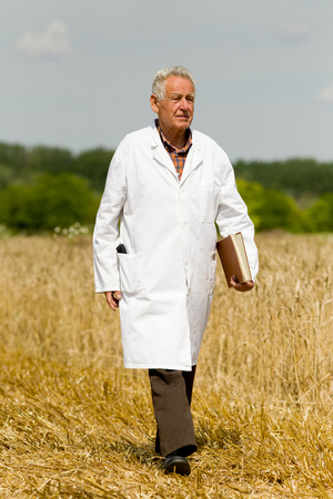 agronomist: Old agronomist in white coat with notebook walking on wheat field