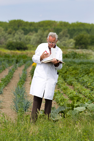 agronomist: Old agronomist in white coat writing notes in book in field