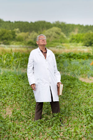 Old agronomist in white coat looking at sky for weather forecast photo
