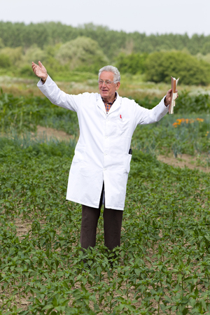 Satisfied old agronomist with spread arms in vegetable garden photo