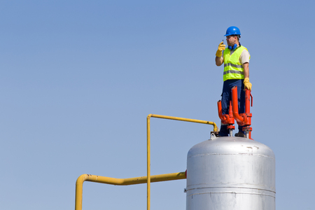 Worker with safety equipment on oil plant photo
