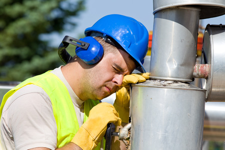 Tired worker fall asleep on oil pipe on plant Stock Photo