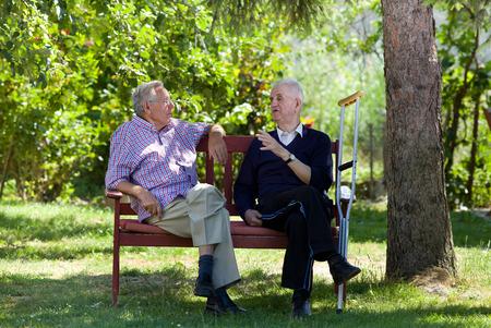 Twee gepensioneerde mannen zitten op een bankje in het park en praten Stockfoto