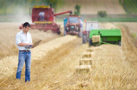 cosechadora: Hacendado joven con ordenador portátil supervisar el trabajo de recolección