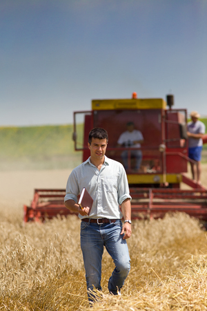 fertile land: Young engineer with notebook standing on wheat field and looking at camera, combine harvester in background  Stock Photo