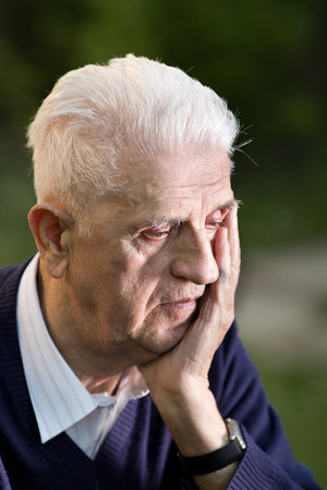 conceived: Portrait of conceived depressed old man with green background