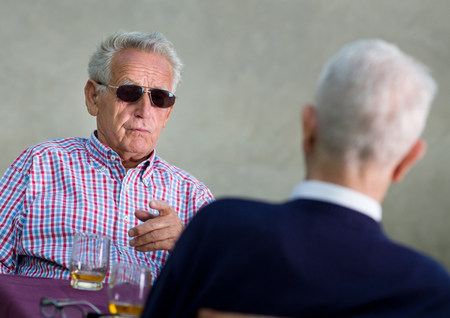 disappoint: Old man with black sunglasses pointing forefinger in another old man Stock Photo