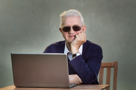 new age music: Older man with sunglasses using laptop at table