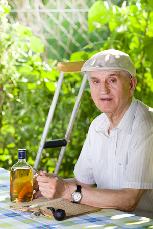 hedonism: Old man hedonist sitting in garden with smoking pipe and whisky on table Stock Photo