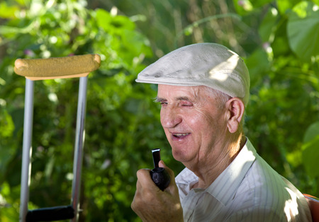 hedonism: Old man smoking pipe and smiling in park Stock Photo