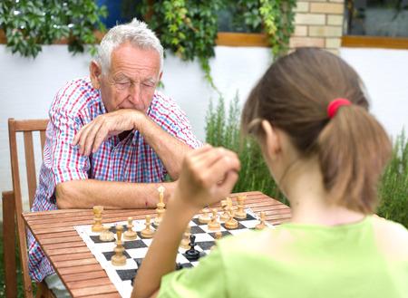 Junges Mädchen, das Schach spielen mit ihrem Großvater im Garten Standard-Bild