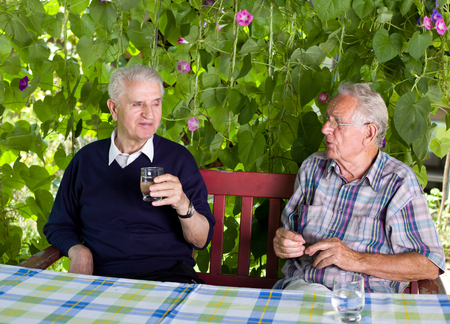 old man portrait: Two senior men sitting on terrace and drinking water