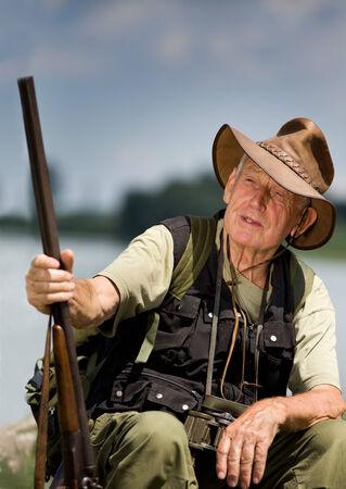 conceived: Senior hunter with shotgun sitting beside lake