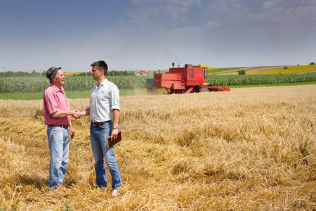 Boer en zakenman schudden handen op tarwe veld Stockfoto