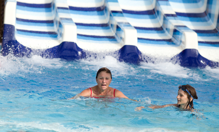 water park: Girl and her grandmother swimming in pool in water park with toboggan in background Stock Photo