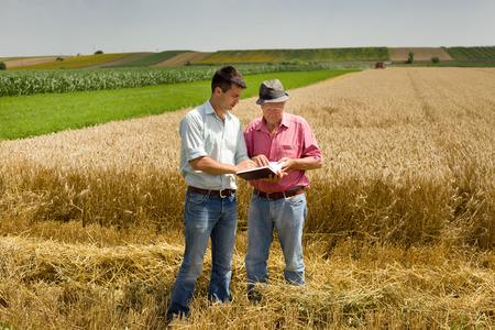 Boer en zakenman kijken naar laptop op tarweveld